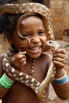 An Indian girl from a snake charmer community plays with a local snake on World Snake Day